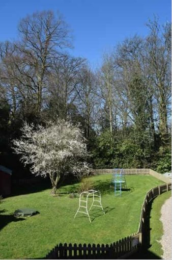 Coach HOuse garden with games, sandpit and rope swings in the trees beyond