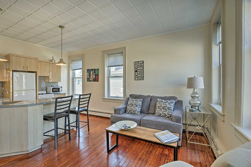 This sleek apartment l is highlighted by rich hardwood floors and modern decor.