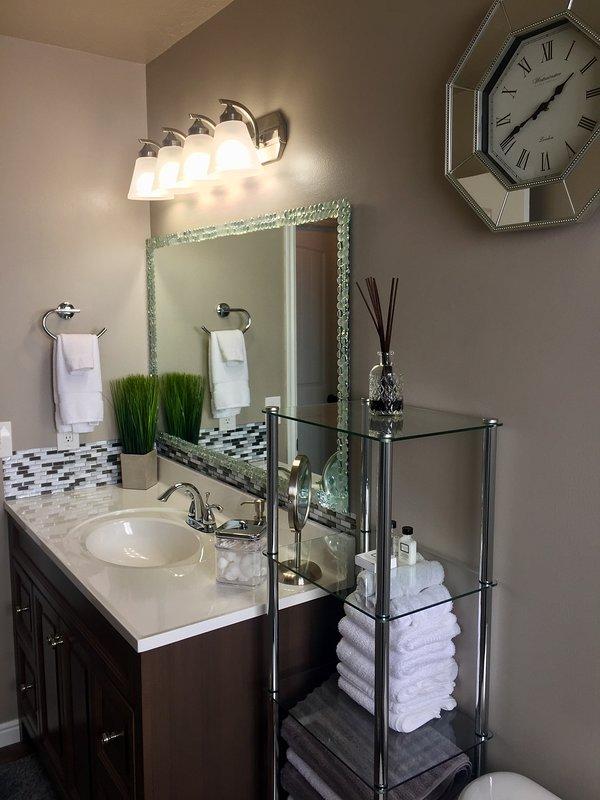 Beautiful & bright bathroom with plenty of fresh linens.