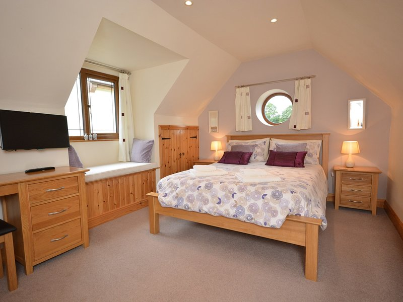 Large king-size bedroom with TV and dressing table