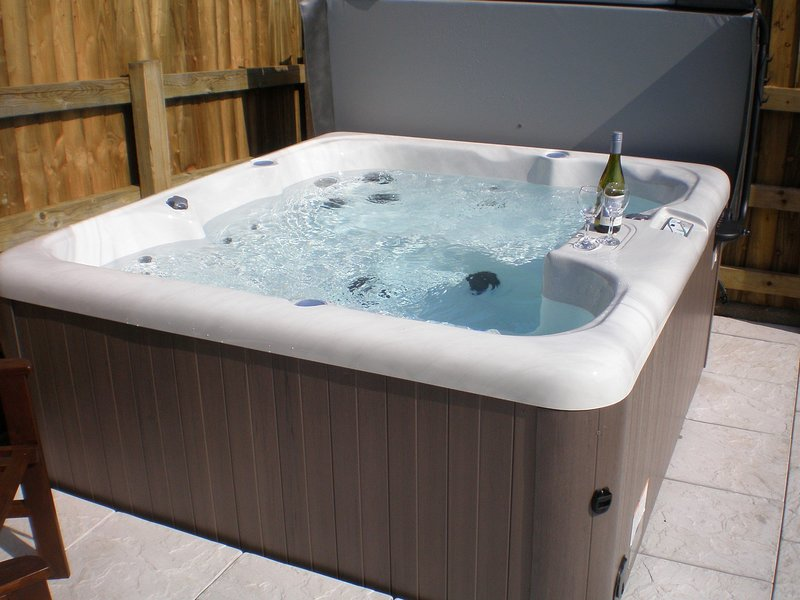 Enjoy the private hot tub in the enclosed garden