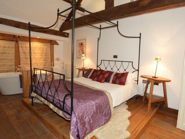 King-Size-Schlafzimmer mit Himmel und freistehender Badewanne