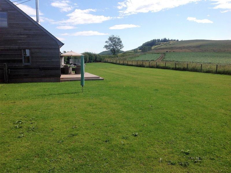 Grand jardin clos à l'arrière avec vue sur les champs et les collines