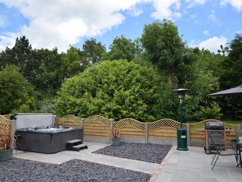 jardín trasero con bañera de hidromasaje y zona de patio