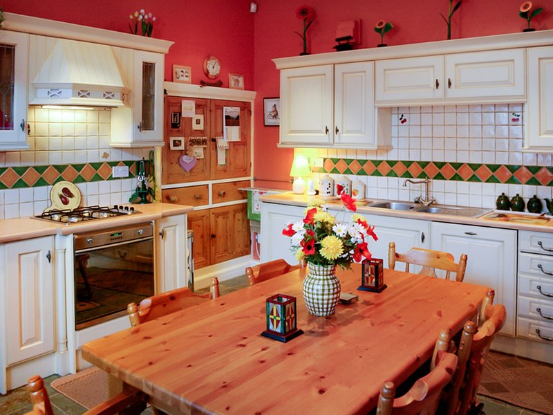 Well equipped kitchen with large table and a sofa