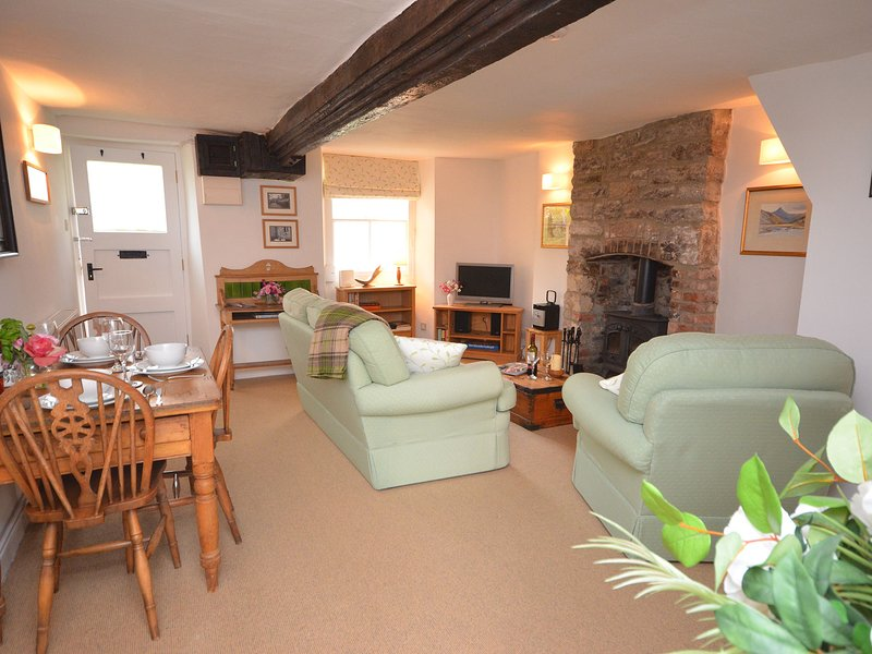 Lounge-Bereich mit freiliegenden Balken und Holzofen