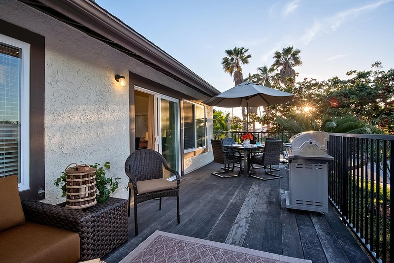 The balcony includes a living area, dining area, grill and peekaboo ocean view.
