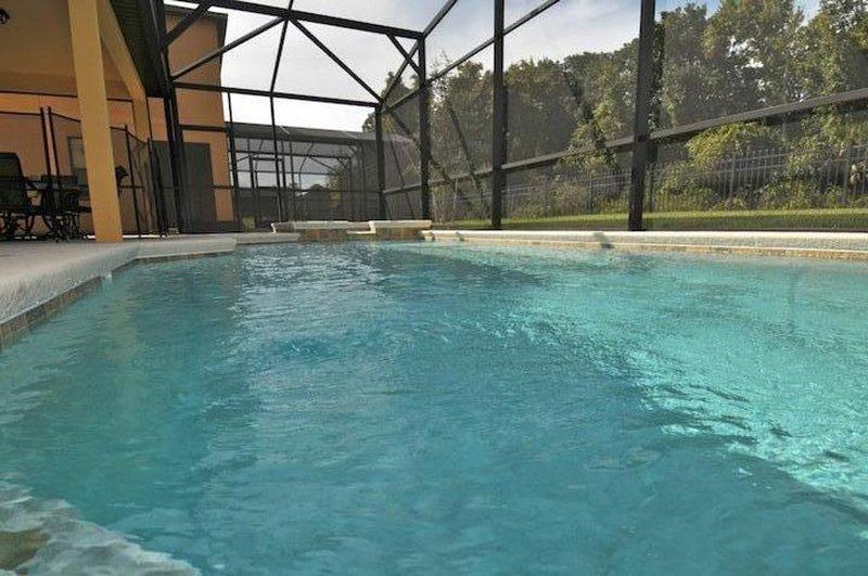piscina de gran tamaño y un spa con vistas a bosque.