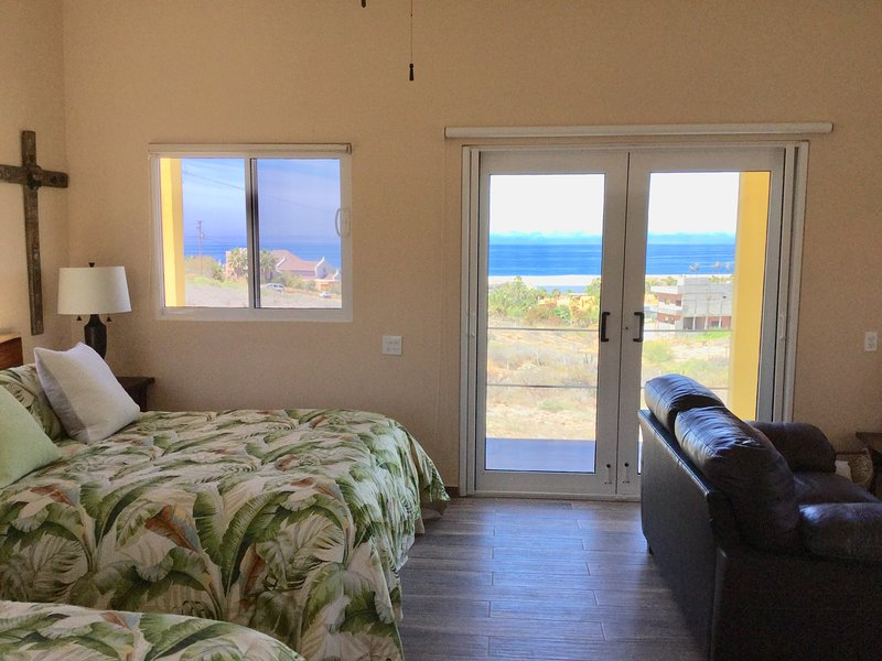 2 queen beds and sitting area with view to ocean