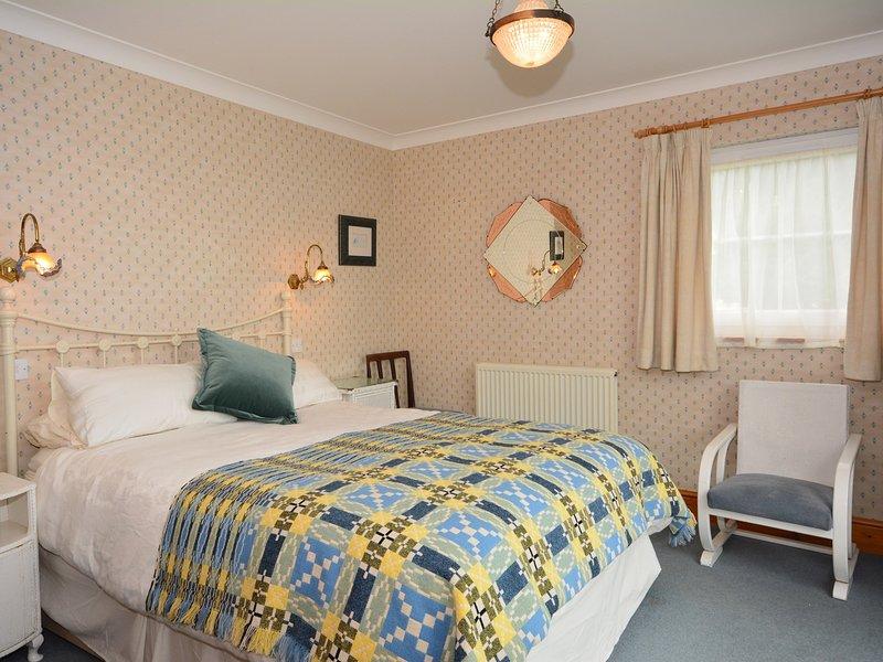 dormitorio con cama extragrande con materiales tradicionales de Gales y vistas al mar