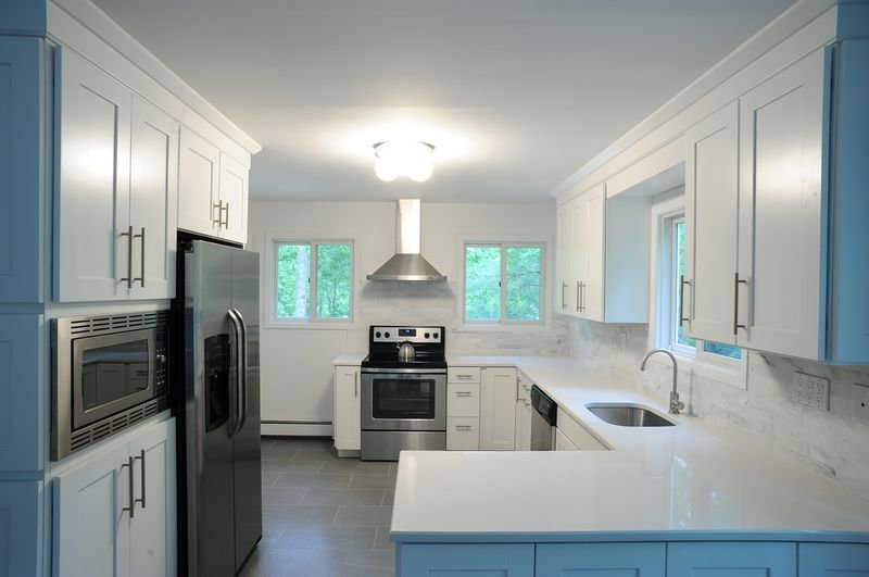 Modern new kitchen with white quartz counter tops, slate tile floor, and marble back spash.