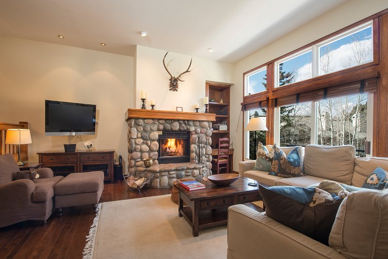 Living room with TV, wood-burning fireplace, and patio access with a gas grill.