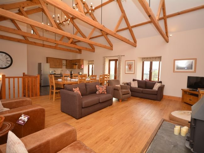 Open-plan living space with woodburner and underfloor heating