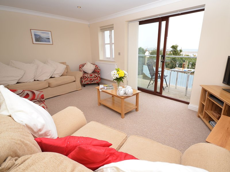 Lounge with doors leading to the decked balcony with estuary views