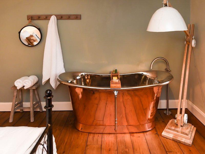 baño de cobre en el dormitorio con cama extragrande