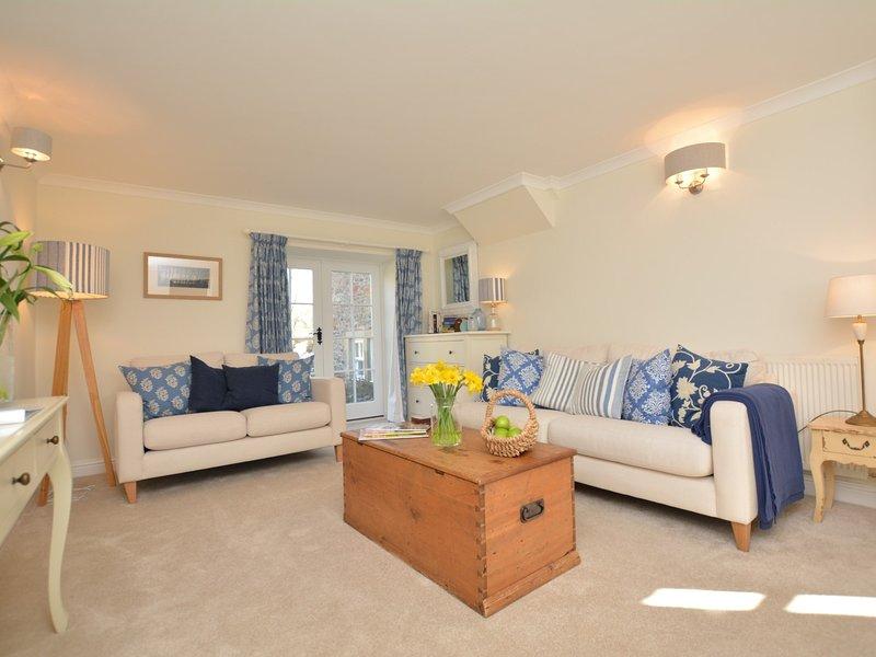 Bella ed elegante salotto con porta finestra che conduce al giardino recintato posteriore