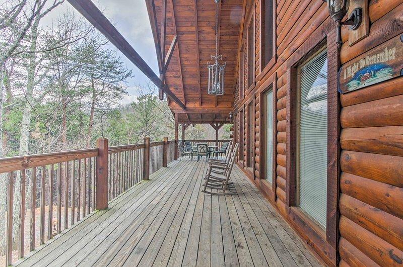 Relax on the wraparound deck with a private hot tub and partial views.