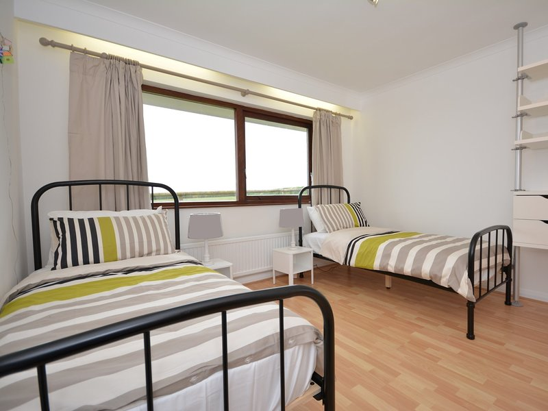 Second twin bedroom with contemporary furnishings and sea views