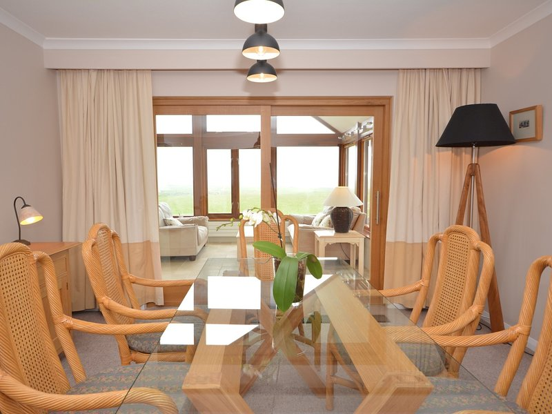 Formal dining area looking towards the conservatory and sea beyond