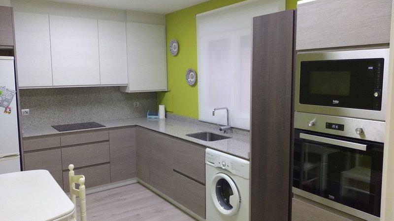 cocina recién reformada con lavavajillas y utensilios necesarios por si se desea cocinar