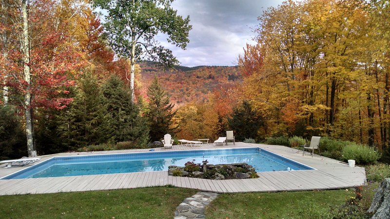 View of swimming pool and mountains during foliage.