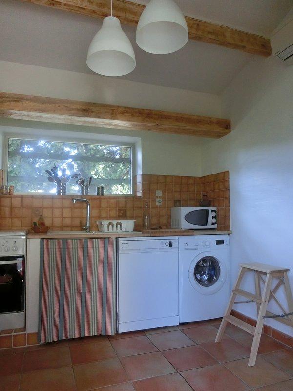 Un'apertura cucina completamente attrezzata su una terrazza coperta per mangiare a qualsiasi ora del giorno