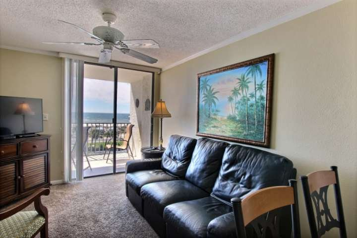 Carpeted living room with ceiling fan, TV/DVD and private balcony access
