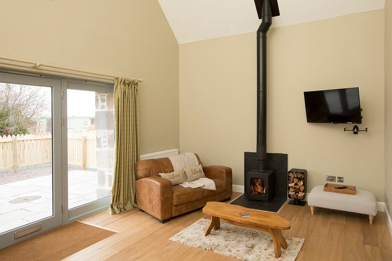 Open plan sitting kitchen space with south facing view and wood burning stove