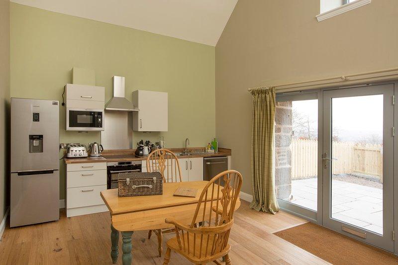 cucina ben attrezzata con piano cottura a induzione, forno, microonde e lavastoviglie
