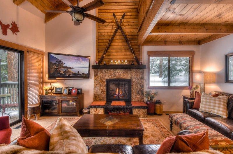 zona soggiorno con camino a gas e grande Smart TV con porte scorrevoli per l'accesso alla veranda