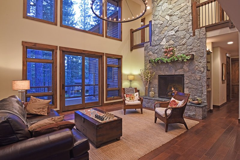 Living room with large stone hearth and large windows for natural light