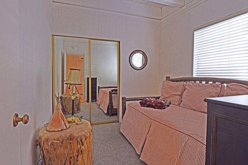 quarto de hóspedes com uma cama de solteiro, além de um rodízio rollout