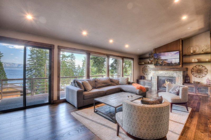 Living room with large TV, gas fireplace and lake views