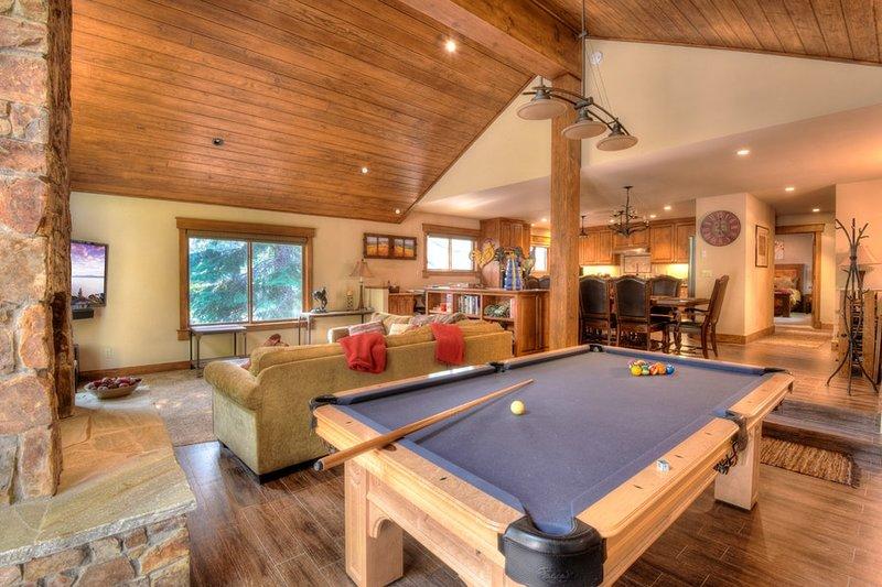 Vista da mesa de bilhar, sala de estar e cozinha na distância