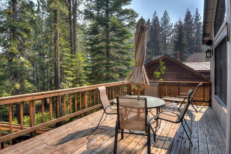 side deck espaçoso, com mobiliário e um guarda-chuva bonito