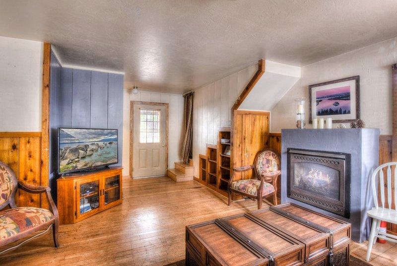 acogedora sala de estar con chimenea de gas y TV de pantalla plana