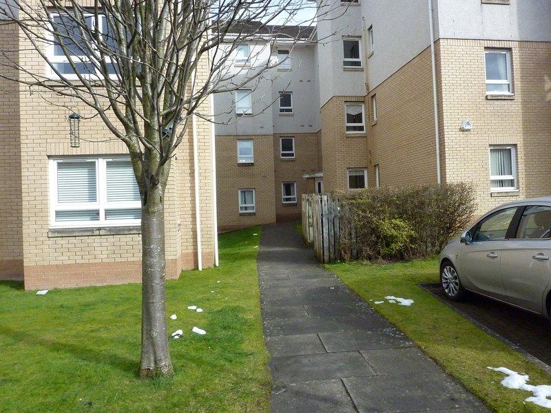 Bakre delen av byggnaden. sedd från privata och gratis boende och gäster parkeringen