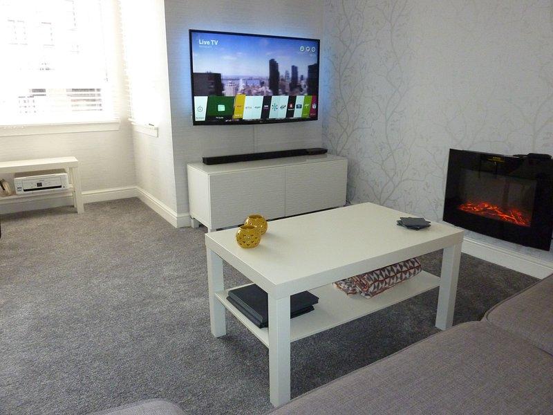 Salón mostrando SMART TV de 50 pulgadas con Netflix, TDT HD, BBC Player y barra de sonido con Bluetooth.