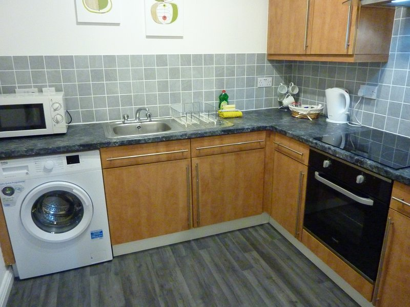 Cocina con todos los electrodomésticos modernos, incluyendo 4 fuegos vitrocerámica, horno eléctrico, microondas, tostadora.