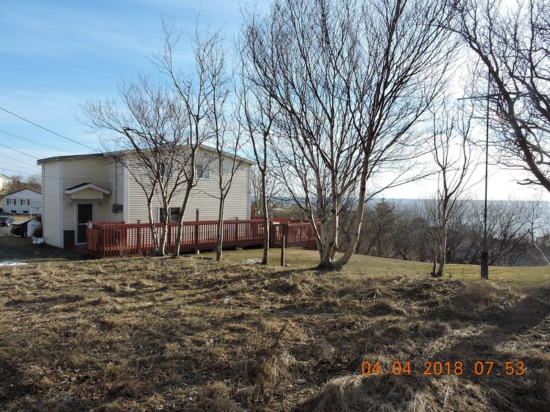 Side view of vacation home in spring of the year. In summer, grass is green and trees are full