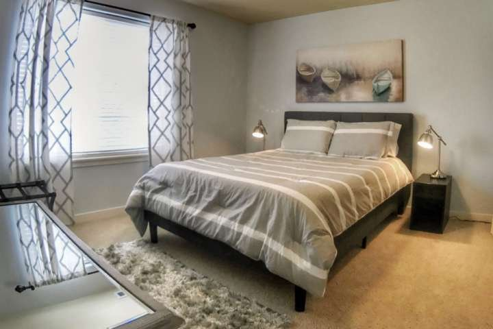 Spacious Guest Bedroom with reading lamps and dresser