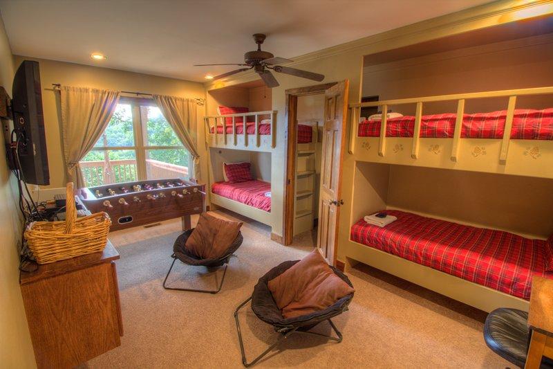 Deerwood Retreat construido en literas en combinación Litera / Play Room con TV de pantalla plana, futbolín y vista. Escaleras divertidas a literas detrás de la puerta.