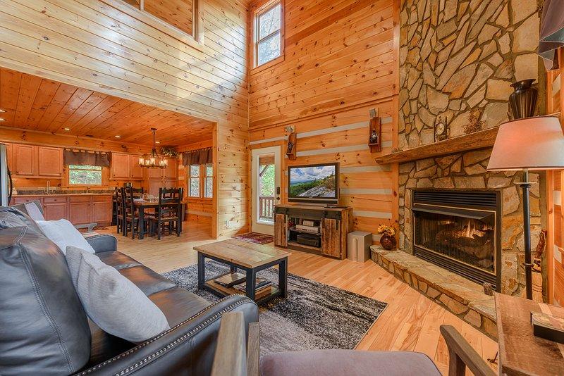 À propos de Time Living Room avec planchers de bois franc et cheminée en pierre