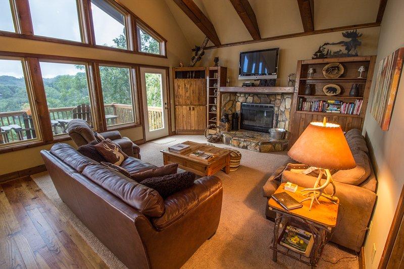 Deerwood Retreat Acogedora sala de estar con chimenea de piedra, sofá de cuero, pared de Windows