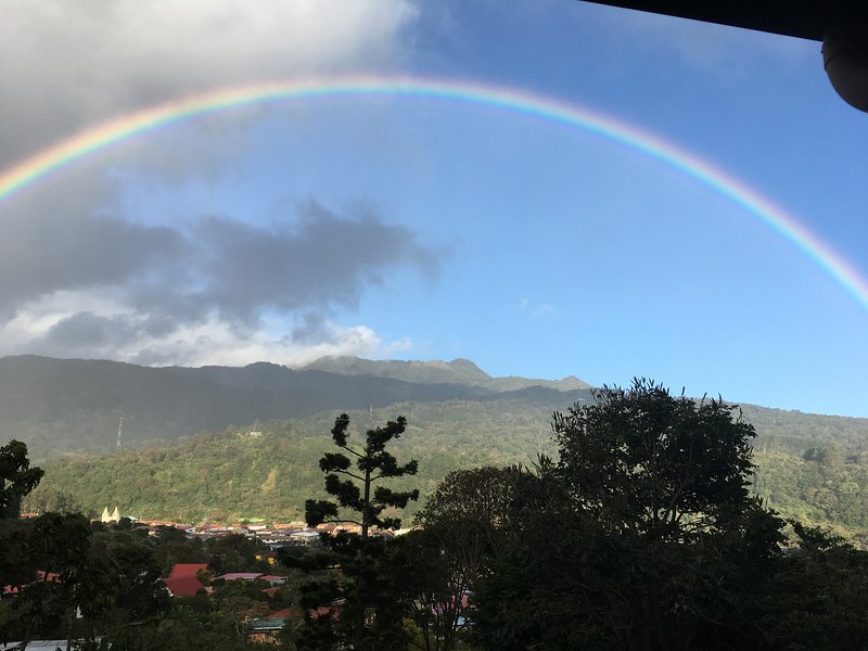 A perfect rainbow arc as seen from Casa Cielo.  Look to the bottom left and you can see the church!