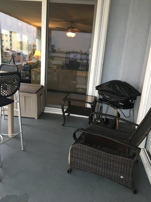 Una parrilla eléctrica Weber al lado de una silla reclinable