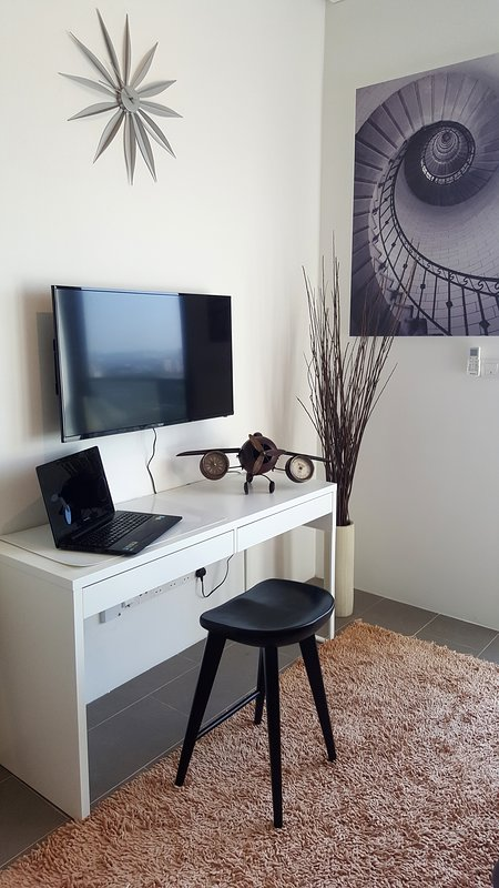 cozy living room with television and working desk