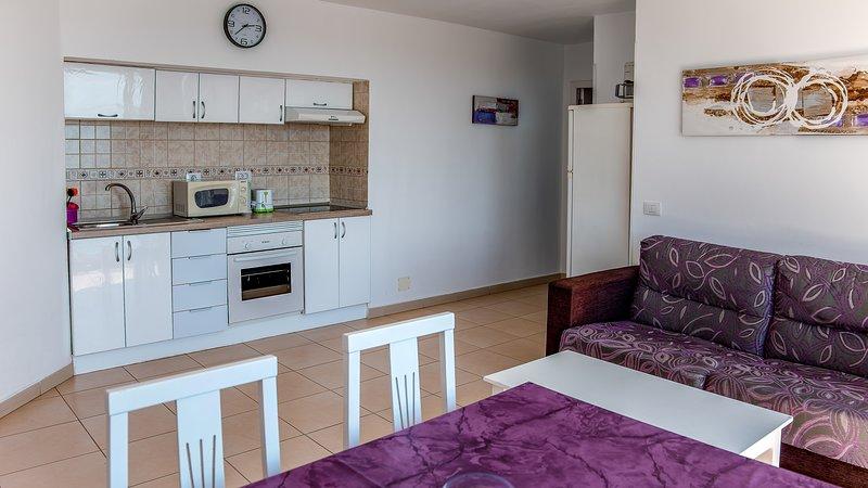 Sala de estar com cozinha aberta, sofá-cama, mesa de jantar, e freezer de 185 cm de altura.