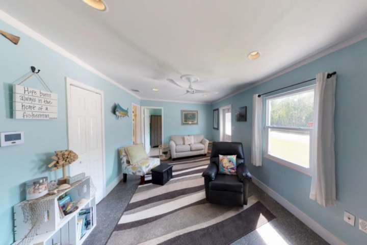 The open living space enjoys comfortable seating, including a relaxing recliner, and lots of gorgeous Florida sunshine.