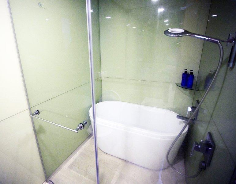 Baño principal con tina de baño, calentador de agua, gratuito champú, gel de ducha y toallas